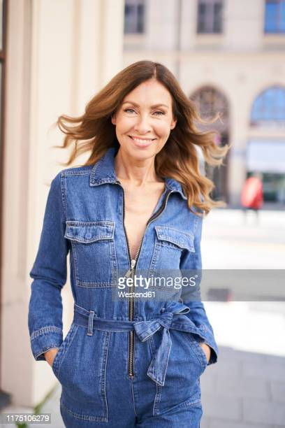 mature woman wearing denim jumpsuit - one mature woman only stock pictures, royalty-free photos & images