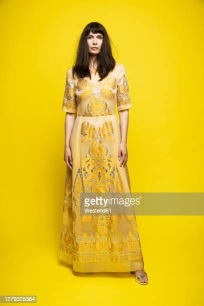 mature woman wearing dress standing against yellow background - fringe dress stock pictures, royalty-free photos & images