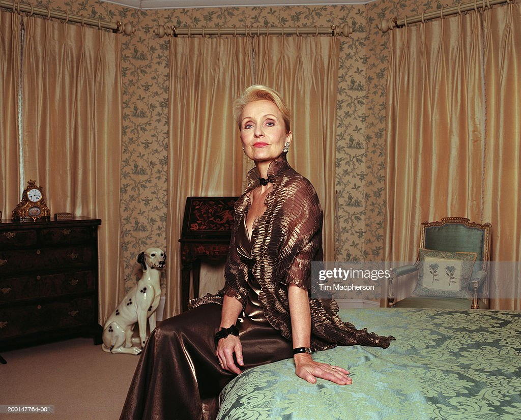 Mature Woman Wearing Evening Dress Sitting On Bed Portrait High-Res Stock Photo -7116