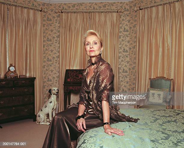 Mature woman wearing evening dress sitting on bed, portrait