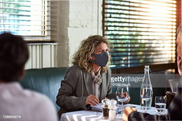 mature woman wearing face covering enjoying meal - human head stock pictures, royalty-free photos & images