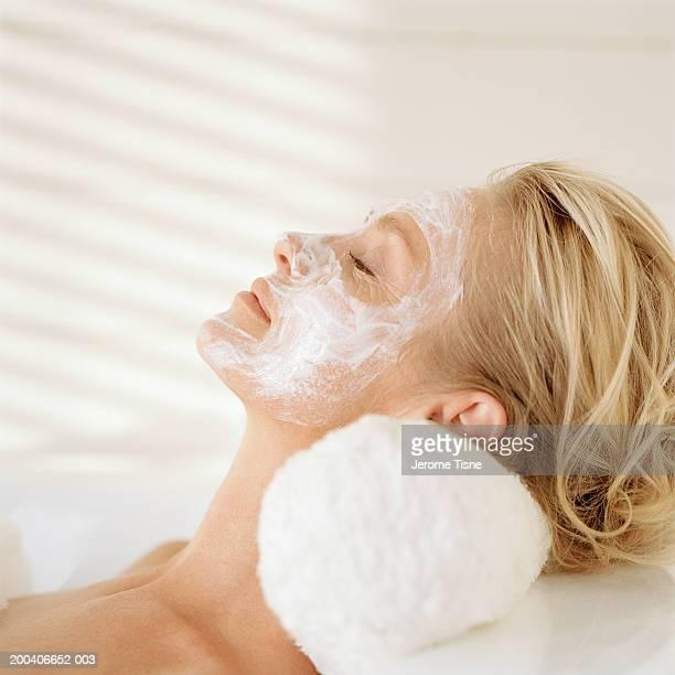 Mature woman wearing facial mask, relaxing in bubble bath, side view