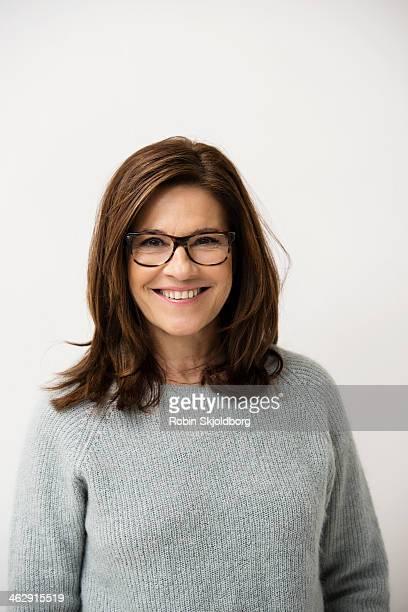 mature woman wearing glases smiling - cheveux bruns photos et images de collection