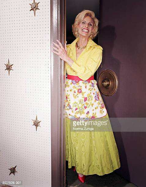 mature woman wearing green dress, standing in doorway, smiling - floral pattern dress stock pictures, royalty-free photos & images