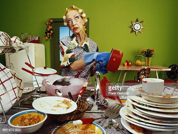 Mature woman wearing hair rollers, washing up dirty dishes