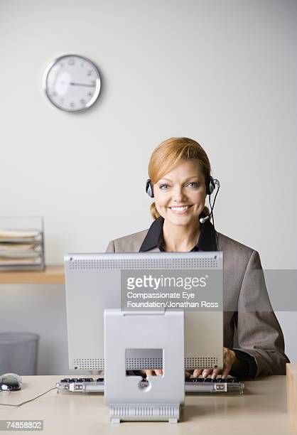 """mature woman wearing headset sitting at desk in office, using computer, smiling, portrait - """"compassionate eye"""" imagens e fotografias de stock"""