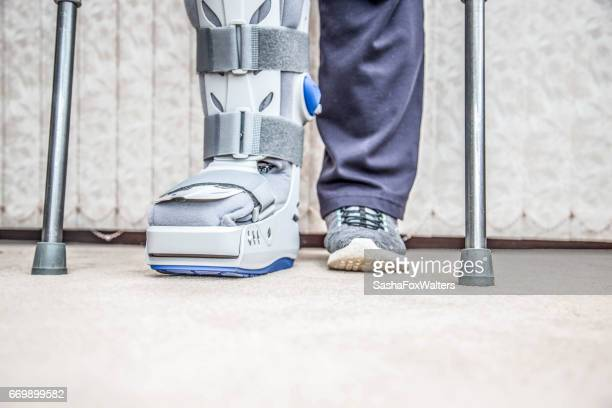 mature woman wearing leg brace and crutches