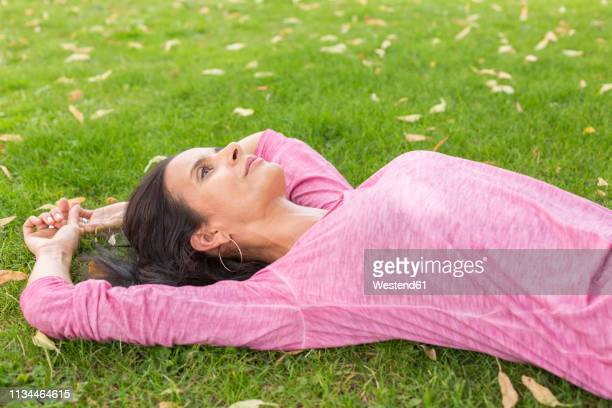 mature woman wearing pink shirt relaxing on a meadow in summer - mindfulness stock pictures, royalty-free photos & images