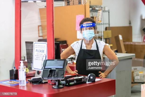 mature woman wearing protective face mask and a face shield posing at her franchise of retail shipping, postal, printing and business service center - post office stock pictures, royalty-free photos & images