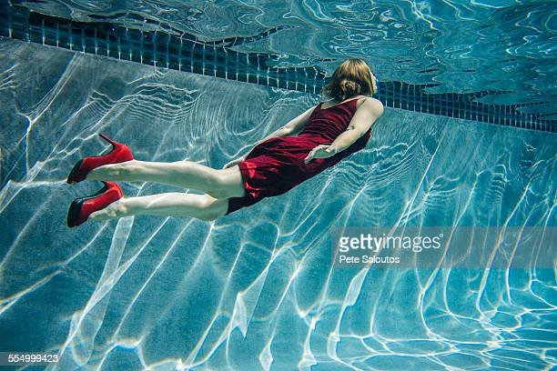 mature woman wearing red dress and high heels, swimming, underwater view - out of context stock pictures, royalty-free photos & images