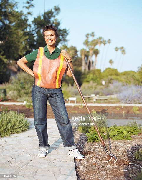 Mature woman wearing safety vest and holding rake in arboretum