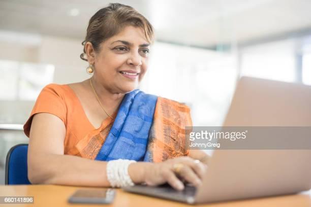 mature woman wearing sari using laptop - sari stock pictures, royalty-free photos & images