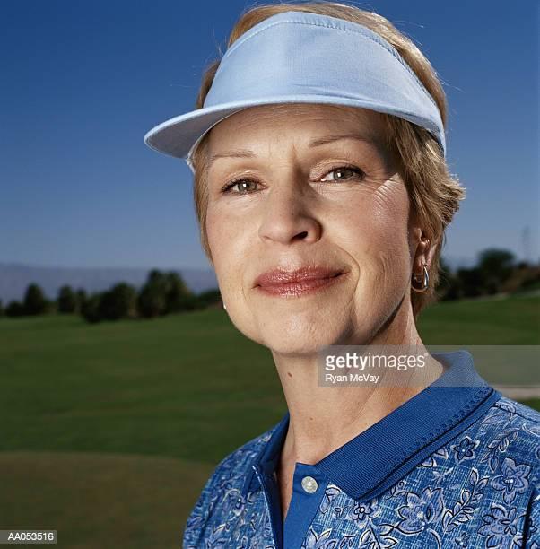 Mature woman wearing sun visor, high section, portrait
