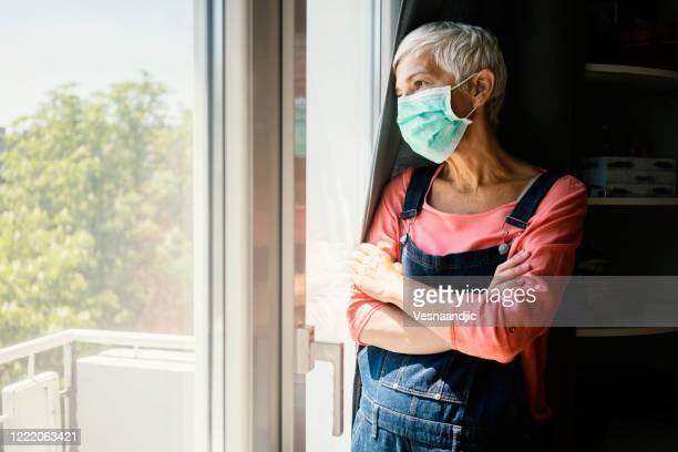 rijpe vrouw die chirurgisch masker draagt - ziektepreventie stockfoto's en -beelden