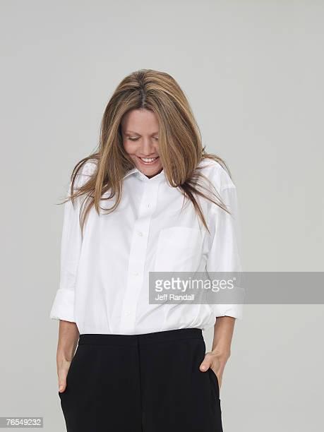 mature woman wearing trousers and white shirt, smiling - hände in den taschen stock-fotos und bilder
