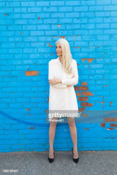 Mature woman wearing white dress standing in front of light blue wall