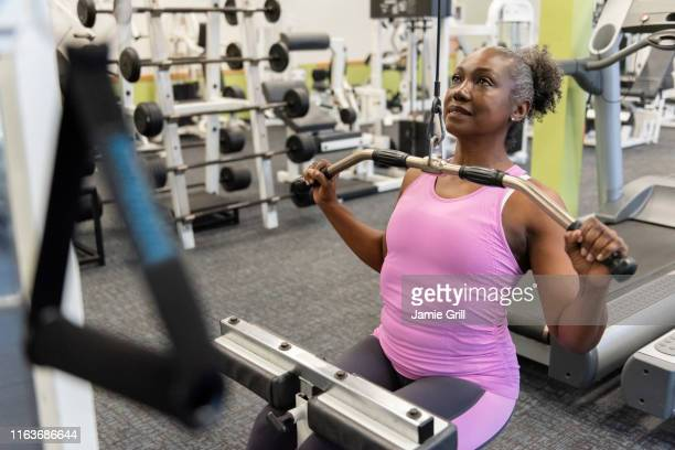 mature woman weight training in gym - strength training stock pictures, royalty-free photos & images