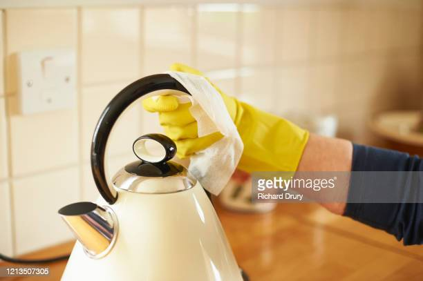 mature woman wiping down her kettle - kettle stock pictures, royalty-free photos & images