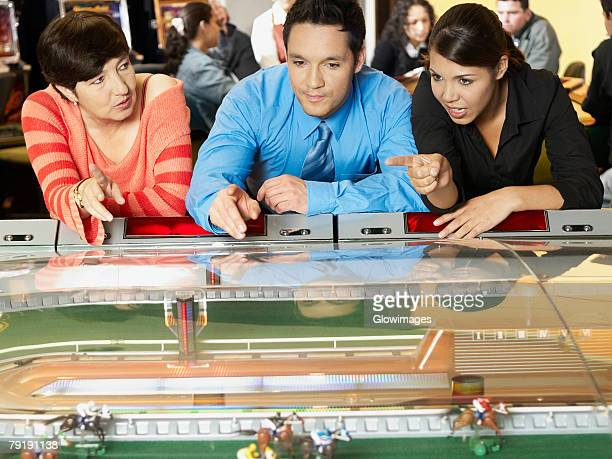 mature woman with a mid adult man and a teenage girl in a casino - teen pokies stock photos and pictures