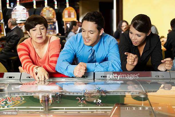 mature woman with a mid adult man and a teenage girl leaning on a casino - teen pokies stock photos and pictures