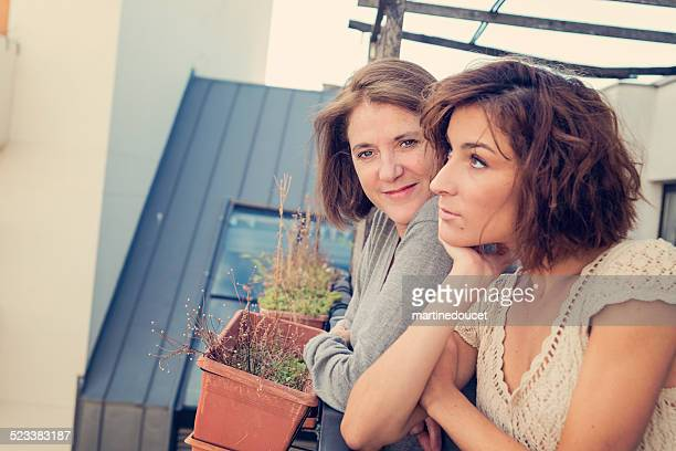Mature woman with adult daughter outdoors on a balcony.