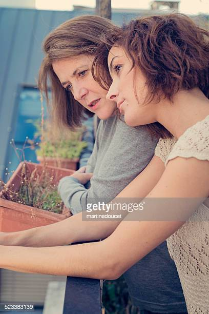 Mature woman with adult daughter talking outdoors on a balcony.