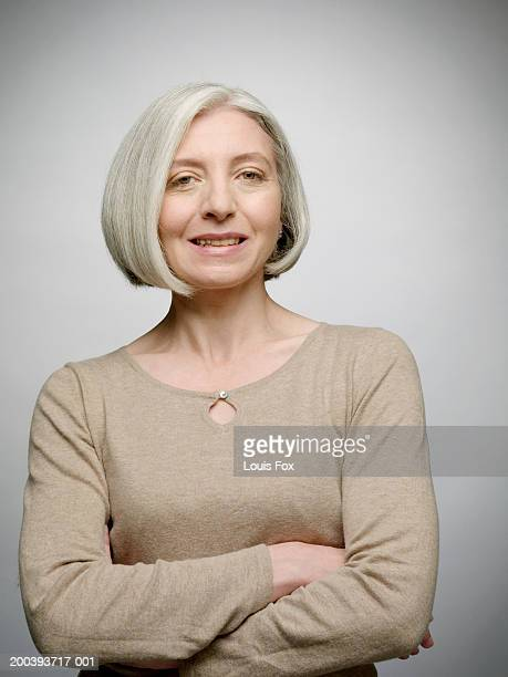 mature woman with arms crossed, smiling, portrait - bobbed hair stock pictures, royalty-free photos & images