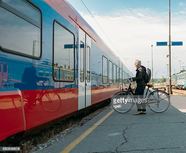 reife frau mit fahrrad auf den öffentlichen verkehrsmitteln. - öffentliches verkehrsmittel stock-fotos und bilder