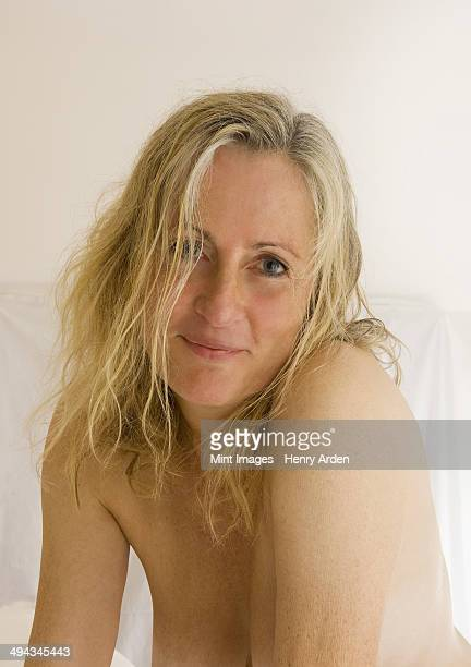 a mature woman with blonde hair and bare skin. - mujeres cuarentonas rubias sin ropa fotografías e imágenes de stock