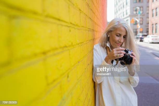 Mature woman with camera leaning against wall