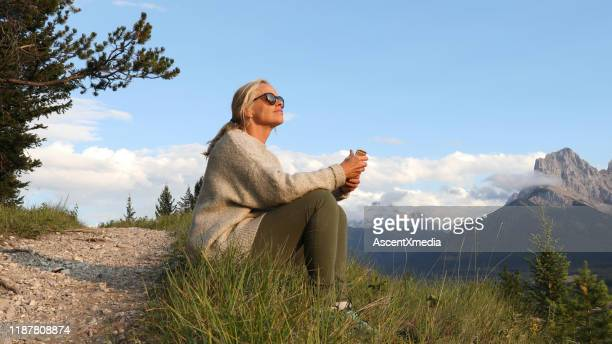 mature woman with cell phone sits by trail at sunrise - early retirement stock pictures, royalty-free photos & images