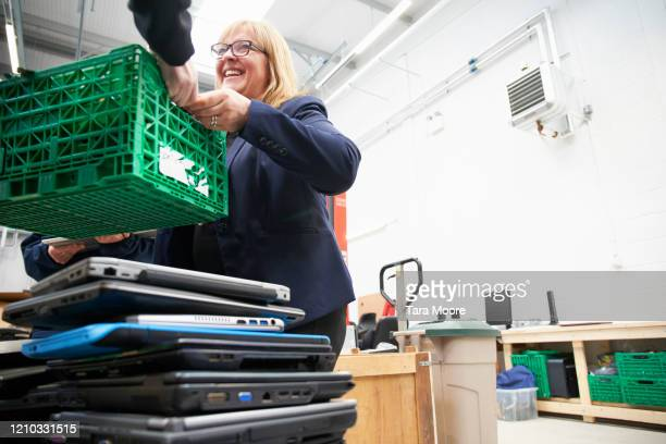 mature woman with crate of used laptops at recycling centre - femalefocuscollection stock pictures, royalty-free photos & images