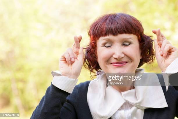 Ältere Frau mit gekreuzten Finger in der Hoffnung auf eine bessere Zukunft