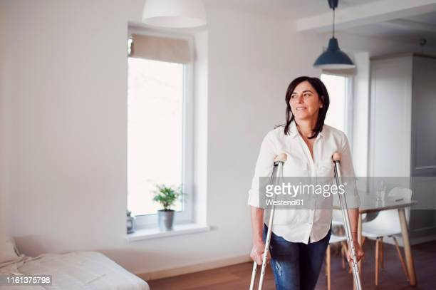 mature woman with crutches, alone at home - 杖 ストックフォトと画像