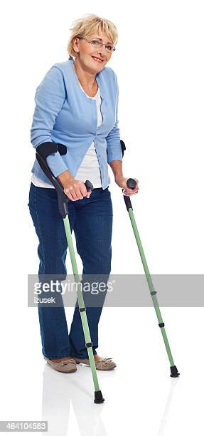 mature woman with crutches - crutch stock photos and pictures