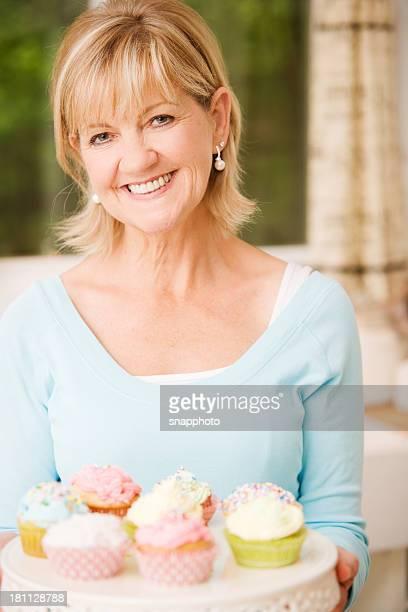 Ältere Frau mit Cupcakes