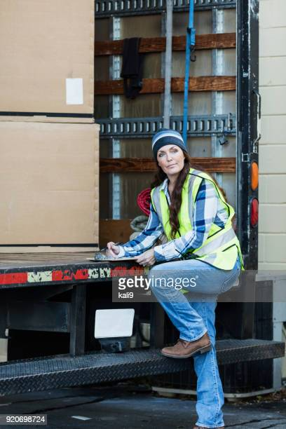 Mature woman with delivery truck, writing on clipboard