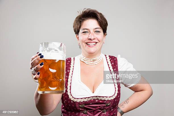 Ältere Frau mit dirndl und ein Glas Bier