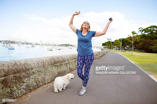 Mature woman with dog and MP3 dancing on street