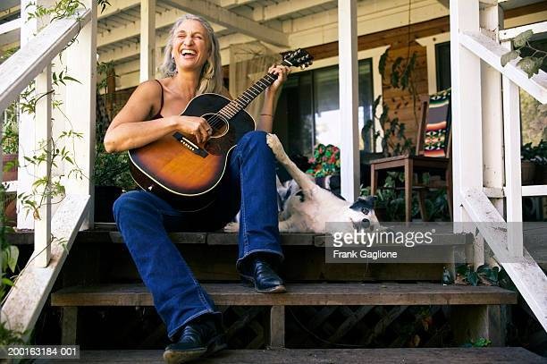 mature woman with dog sitting on porch, holding guitar, smiling - one animal stock pictures, royalty-free photos & images