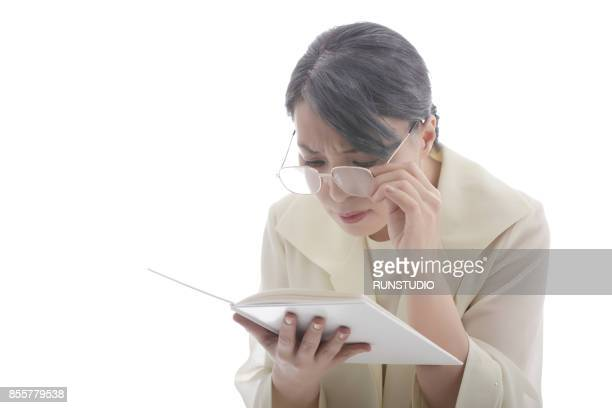 mature woman with eye glasses trying to read book - reading glasses stock pictures, royalty-free photos & images