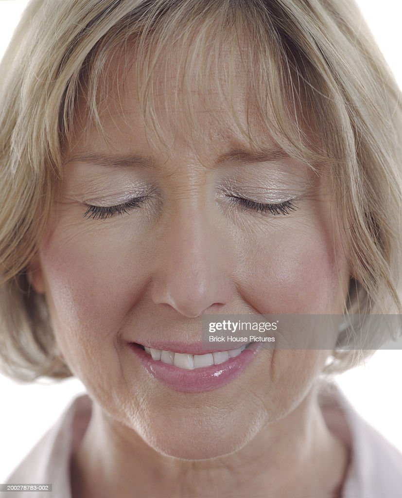 Mature Woman With Eyes Closed Smiling Closeup High-Res