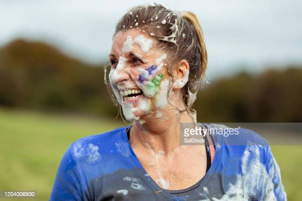 mature woman with face covered in foam at charity event - charity and relief work stock pictures, royalty-free photos & images