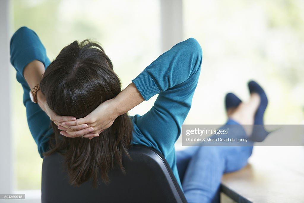 Mature woman with feet up on desk : Stock Photo