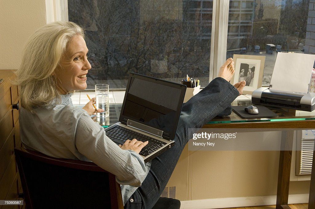 Mature Woman With Feet Up Working On Laptop Stock Photo