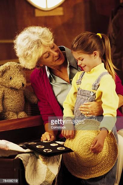 Mature woman with granddaughter looking at memorabilia