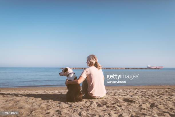 mature woman with gray hair relaxing on beach with dog - donna di spalle al mare foto e immagini stock