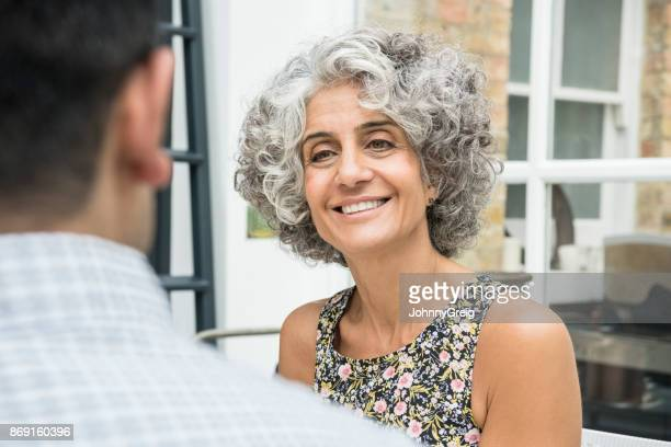 Mature woman with grey curly hair and floral top smiling and talking to man