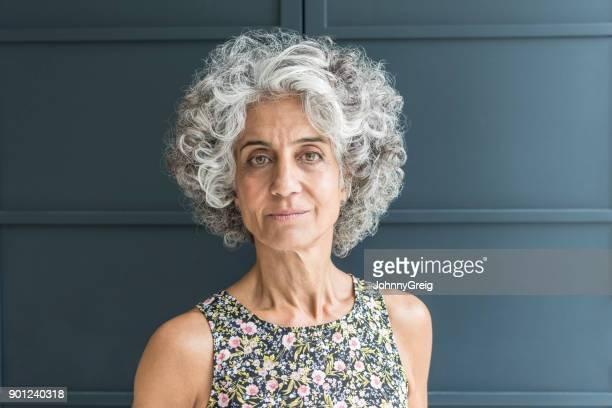 femme d'âge mûr aux cheveux bouclé regardant la caméra - robe à motif floral photos et images de collection