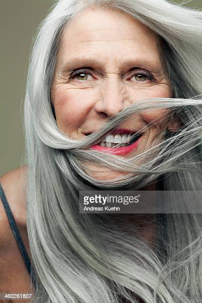 Mature woman with hair blown across face, smiling.